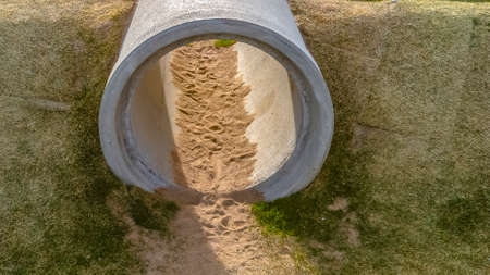 Panorama Crawl tunnels made of concrete cylinder pipes at a sunny playground