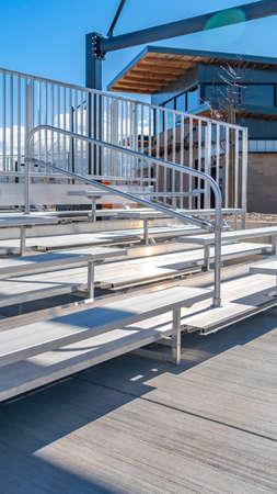 Vertical frame Bleachers with railings against a building and cloudy blue sky