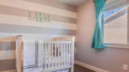 Panorama Interior of a nursery with white crib and monogram letters on the striped wall