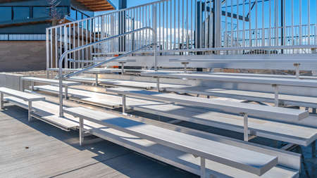 Panorama Bleachers with railings against a building and cloudy blue sky Stock Photo