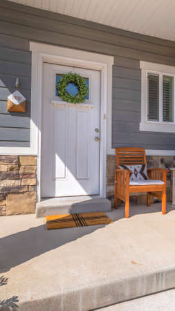 Vertical Facacde of a home with furniture on the welcoming sunlit porch
