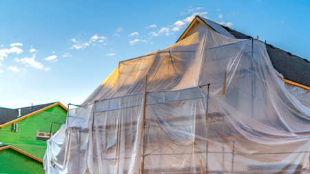 Panorama Plastic sheet covering an unfinished house and scaffoldings against blue sky Archivio Fotografico