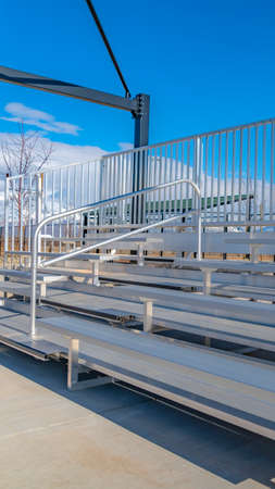 Vertical frame Raised tiered rows of benches with railings at a sports filed on a sunny day