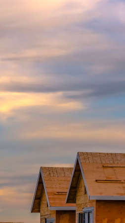 Vertical Close up of a house under construction against cloudy sky at sunset