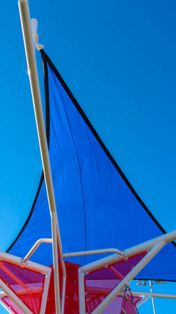 Vertical frame Thin triangular blue roof supported by smooth white poles against clear sky Stock Photo