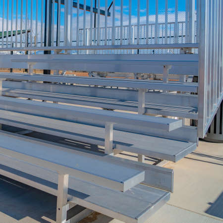 Square frame Raised tiered rows of benches with railings at a sports filed on a sunny day