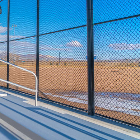 Square frame Sunlit bleachers overlooking a vast sports field on the other side of the fence Stock Photo