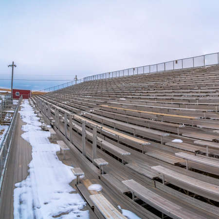 Square Row of tiered benches on a sports arena under a cloudy sky in winter