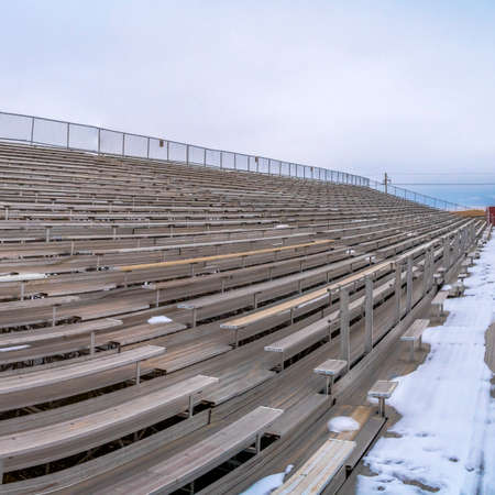 Square frame Row of tiered benches on a sports arena under a cloudy sky in winter Stock Photo