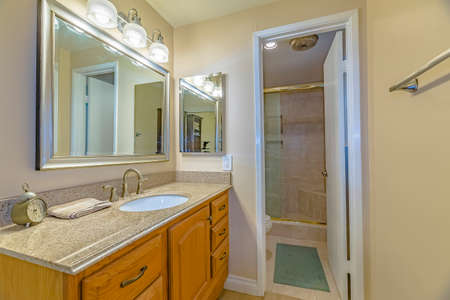 Vanity unit with brown wooden cabinets and bright lights inside a bathroom