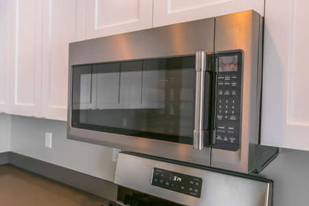 Close up of a microwave and white cabinets mounted on the wall of a kitchen