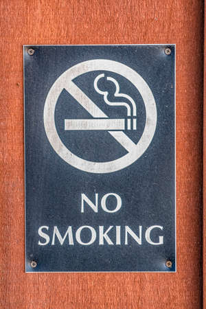 Close up of a No Smoking sign screwed to a reddish brown wood surface Stock Photo