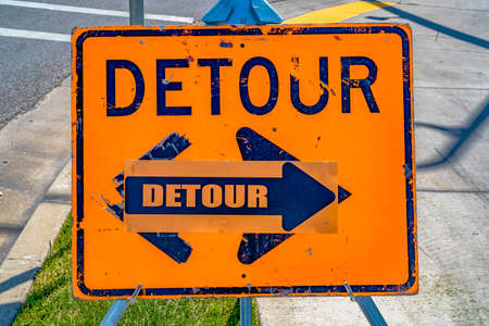Close up of a weathered orange and blue Detour sign with arrow
