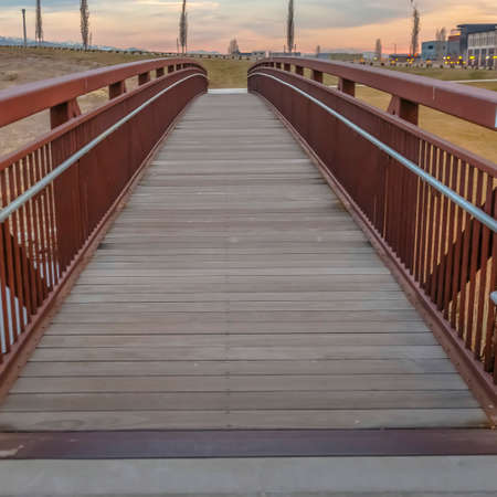 Frame Square Close up of a bridge with a wooden deck and brown metal guardrails