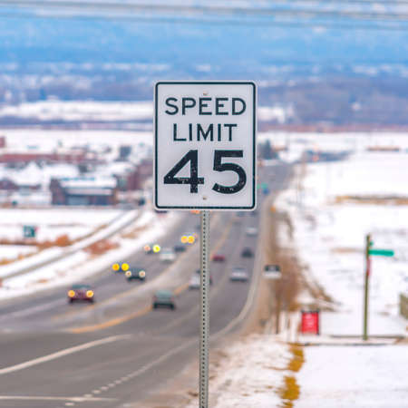 Square Close up of a Speed Limit sign at a highway surrounded with snow in winter