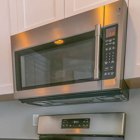 Square Range and wall mounted microwave inside the kitchen with brown wooden floor Imagens