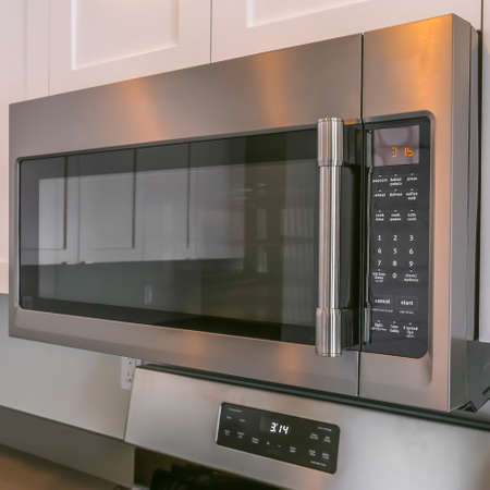Square Close up of a microwave and white cabinets mounted on the wall of a kitchen
