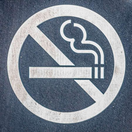 Square Close up of a No Smoking sign screwed to a reddish brown wood surface