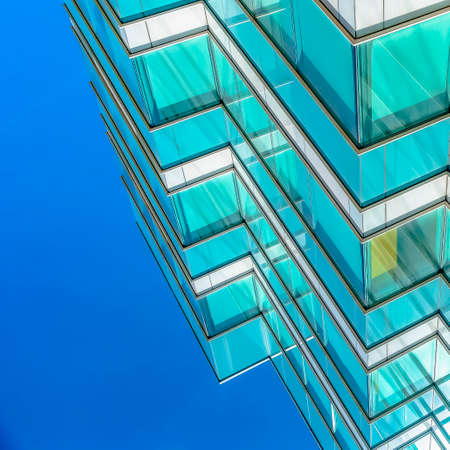 Square Close up of an office building exterior against blue sky on a sunny day Stock Photo