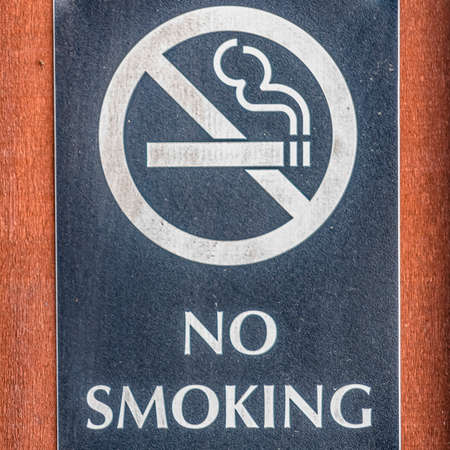 Frame Square Close up of a No Smoking sign screwed to a reddish brown wood surface Reklamní fotografie