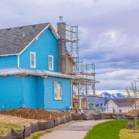Frame Square Blue casa in costruzione con impalcature contro la montagna e il cielo nuvoloso Archivio Fotografico