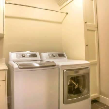 Square Washing machine and dryer inside the laundry room of a house