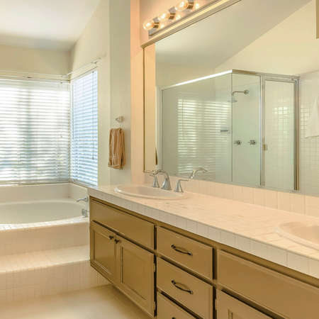 Square Bathtub and double vanity unit inside the well lighted bathroom of a home