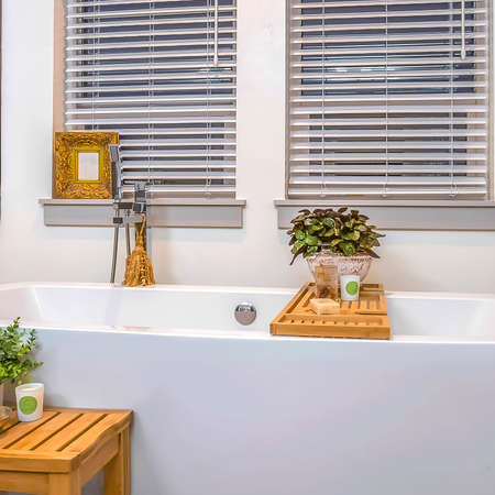 Frame Square Relaxing bathroom interior with spotless white bathtub mirror and two windows Stock Photo