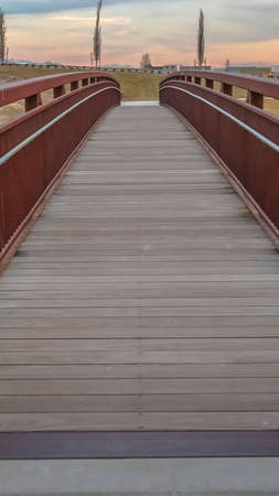 Panorama Close up of a bridge with a wooden deck and brown metal guardrails