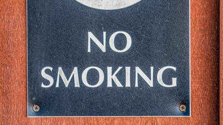 Panorama frame Close up of a No Smoking sign screwed to a reddish brown wood surface