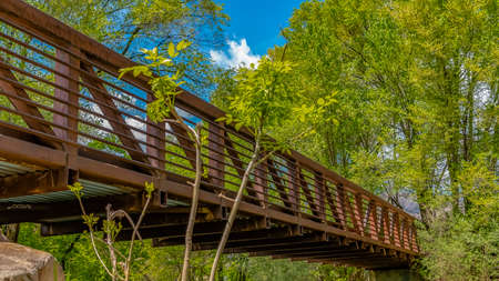 Panorama frame Bridge with metal guardrails over the glistening water at Ogden River Parkway Stock Photo