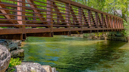 Panorama frame Bridge over glistening river with rocks on the bank at Ogden River Parkway Stock Photo