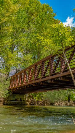 Panorama Bridge with metal guardrails over the glistening water at Ogden River Parkway