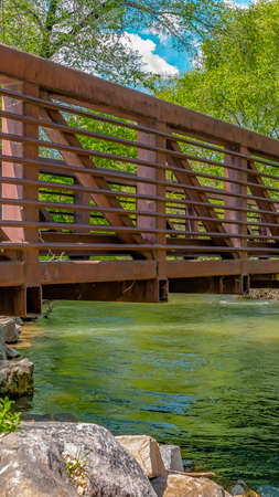 Panorama Bridge over glistening river with rocks on the bank at Ogden River Parkway Stock Photo