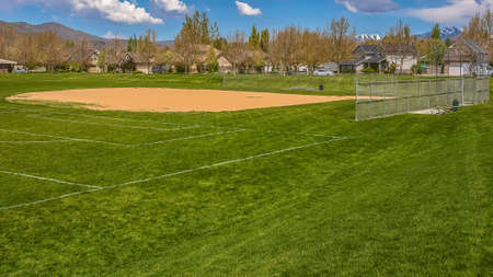 Panorama frame Baseball or softball field with buildings and trees beyond the grassy terrain