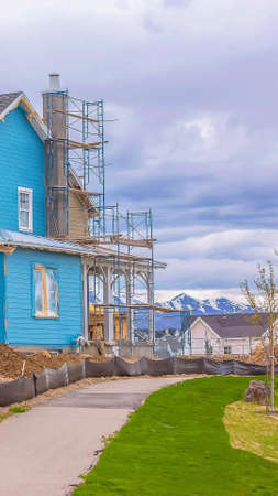 Panorama frame Blue house under construction with scaffoldings against mountain and cloudy sky