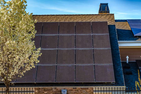 Solar panel on the dark pitched roof of a house against blue sky on a sunny day Stockfoto