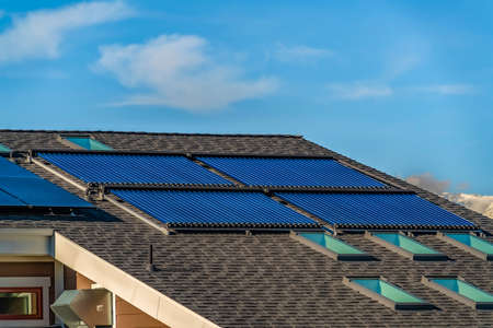 Pitched roof with solar water heater solar panels and skylights Stockfoto