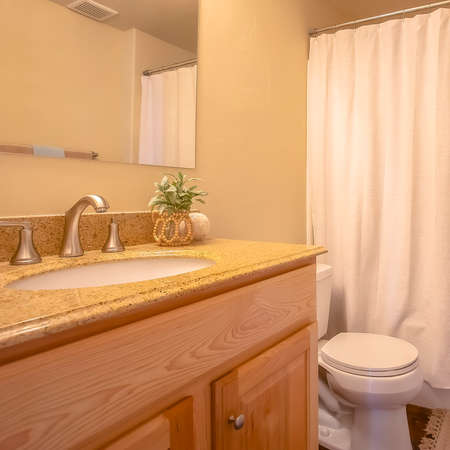 Square frame Toliet and vanity area inside a bathroom with towel rod and mirror on the wall