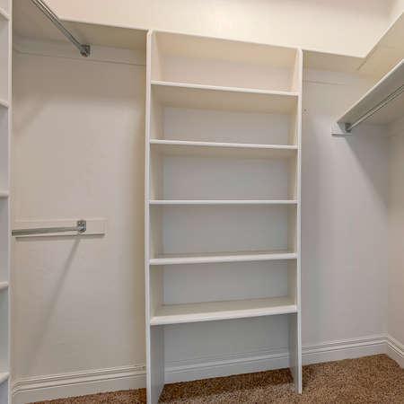 Kwadratowe wnętrze garderoby z półkami i lśniącymi pręcikami na ubrania