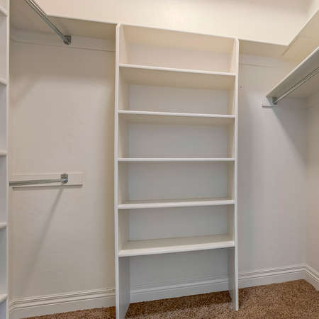 Square Interior of a walk in closet with shelves and shiny garment rods