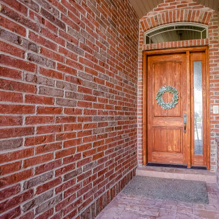 Square frame Rustic wooden door with wreath sidelight and arched transom window Stock Photo