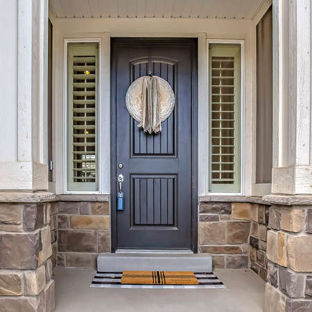 Square frame Home entrance with a gray front door in the middle of sidelights with blinds