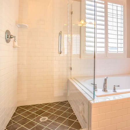 Square Built in bathtub and shower stall with glass door inside a bathroom