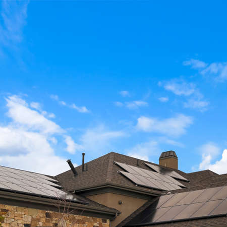Square Cloudy blue sky over a home with solar panels on the pitched roof 스톡 콘텐츠
