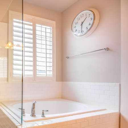 Square frame Built in bathtub and shower stall with glass door inside a bathroom