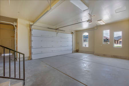 Empty garage with white doors as well as arched and rectangular windows