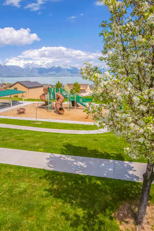 Playground and residential area against lake and mountain under cloudy blue sky