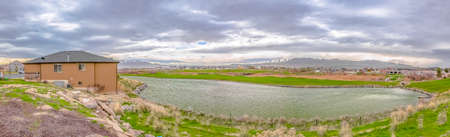 Homes and grassy ground around a silvery lake under sky filled with gray clouds 스톡 콘텐츠