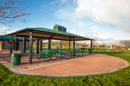 Covered picnic area on a scenic park under cloudy blue sky 스톡 콘텐츠